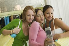 3 Girl friends Posing for Camera Phone Picture in clothing store Stock Photos
