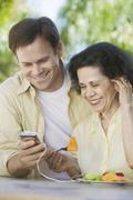 Son Showing Mother How to Use MP3 Player - stock photo