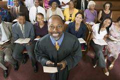 Preacher Holding Bible With Congregation Sitting In Church - stock photo
