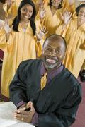 Minister at altar with Bible gospel choir in background portrait - stock photo