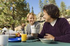 Women eating at picnic table in campground - stock photo
