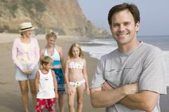 Portrait of man on beach with family - stock photo