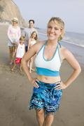 Portrait of woman on beach with family - stock photo