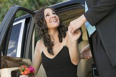 Well-dressed teenager girl being helped out of limo by date Stock Photos