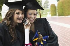 Two graduates using cell phone outside Stock Photos