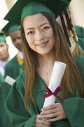 Female Graduate Holding Diploma With Friends In Background Stock Photos