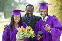Father With Two Graduates Outside Stock Photos