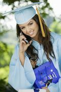 Female Graduate Using Cell Phone - stock photo