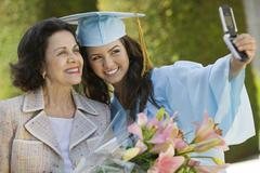 Graduate And Grandmother Taking Picture With Cellphone Stock Photos