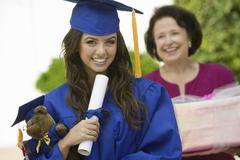 Graduate Holding Teddy Bear And Diploma Outside - stock photo