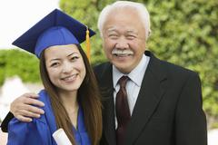 Portrait Of A Female Graduate And Grandfather Stock Photos