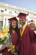 Two Graduates Holding Diploma And Flowers - stock photo