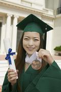 Graduate Holding Diploma And Medal Outside University Stock Photos