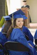 Female Graduate With Friends Attending Graduation Ceremony - stock photo