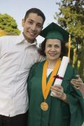 Female Graduate Holding Degree With Son - stock photo