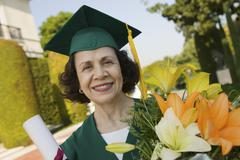 Female Graduate Holding Degree And Bouquet Stock Photos