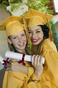 Female Students With Diplomas Embracing Each Other In Campus Stock Photos
