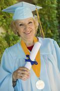Senior Graduate Holding Diploma Outside - stock photo