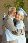 Senior Female Graduate Embracing Man Stock Photos