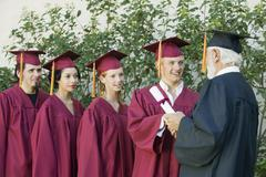 Graduates Collecting Certificate From Dean - stock photo