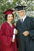 Female Graduate Holding Certificate With Dean Stock Photos