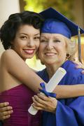 Female Graduate Embracing Granddaughter Stock Photos