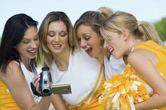 Cheerleaders Watching Video Through Handycam - stock photo