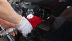 Fueling station service man glove pulls out pistol car gas Stock Footage