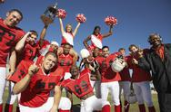 Stock Photo of Football Team With Cheerleaders And Coach Celebrating Success On Field