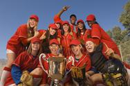 Softball Team And Coach With Trophy Celebrating Against Sky Stock Photos