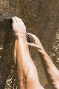 Rock Climber's Hand Grasping Hold On Cliff - stock photo