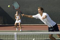 Doubles Player Hitting Tennis ball With Forehand Stock Photos