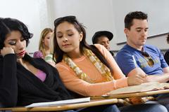 Stock Photo of Woman Peeping Into Friend's Notes During Class Lecture