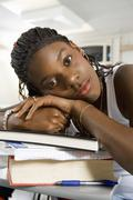 Woman Resting On Stack Of Books In Classroom - stock photo