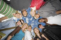 College Students Forming Huddle Against Cloudy Sky Stock Photos