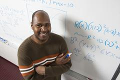Teacher Solving Math's Equations On Whiteboard Stock Photos
