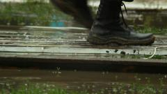 Massive military boots step on wooden platform over water, flood - stock footage
