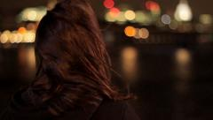 Lady looks out onto night city Stock Footage