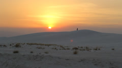 Man in Silhouette Walks on White Sand Dune at Sunset Stock Footage