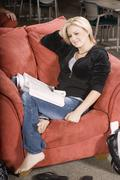 Relaxed Young Woman Sitting On An Armchair Stock Photos