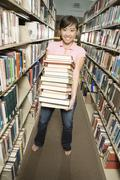 Student Carrying Stack Of Books In The Library Stock Photos