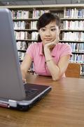 Stock Photo of Bored Female Student Using Laptop