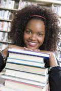 Female Student Leaning On Stack Of Books - stock photo