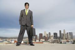 Businessman Standing On Building Rooftop - stock photo