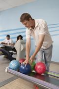 Stock Photo of Young Man At Bowling Alley Choosing Ball
