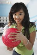 Young Woman Holding Ball At Bowling Alley - stock photo