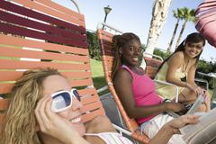Happy Young Women Relaxing On Deck Chair - stock photo