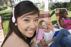 Asian Female Listening To Music On IPod - stock photo
