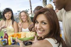Stock Photo of Woman Serving Snacks To Friends