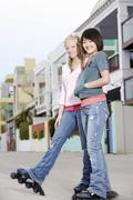 Female Friends Rollerblading On Street Stock Photos